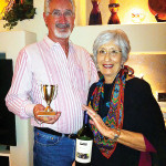 Fred and Susan Henderson display the Tuesday Taster's award winning wine for the month of April.