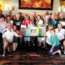 Wisconsin Club members got together at The Grill for fun, football and food. They are shown with the many school supplies they donated and gave to the After Schoolers group for local children.