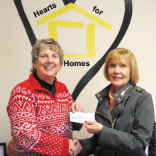 Hearts for Homes director Susan Frank receives check from Mala Bowdouris.