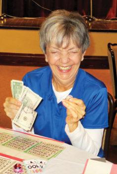 Joan Petre grinning ear to ear over her Bingo winnings