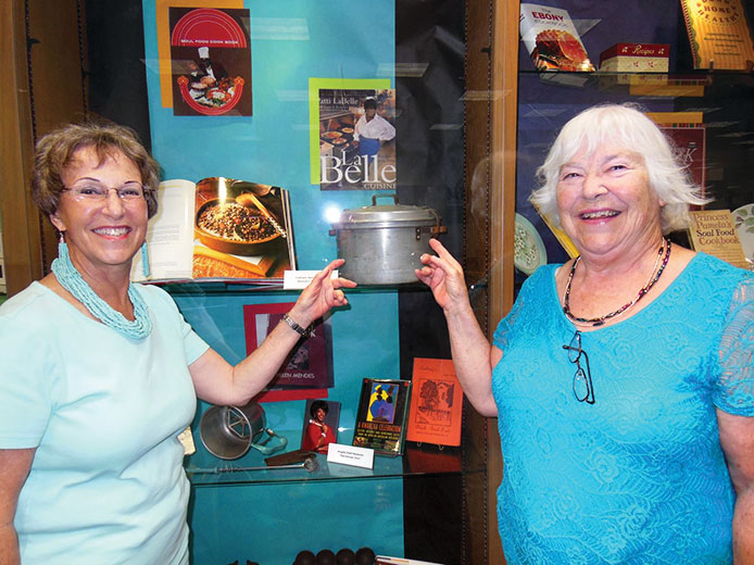 Left to right: Carol Solow and Mary Mullins point to an early pressure cooker.