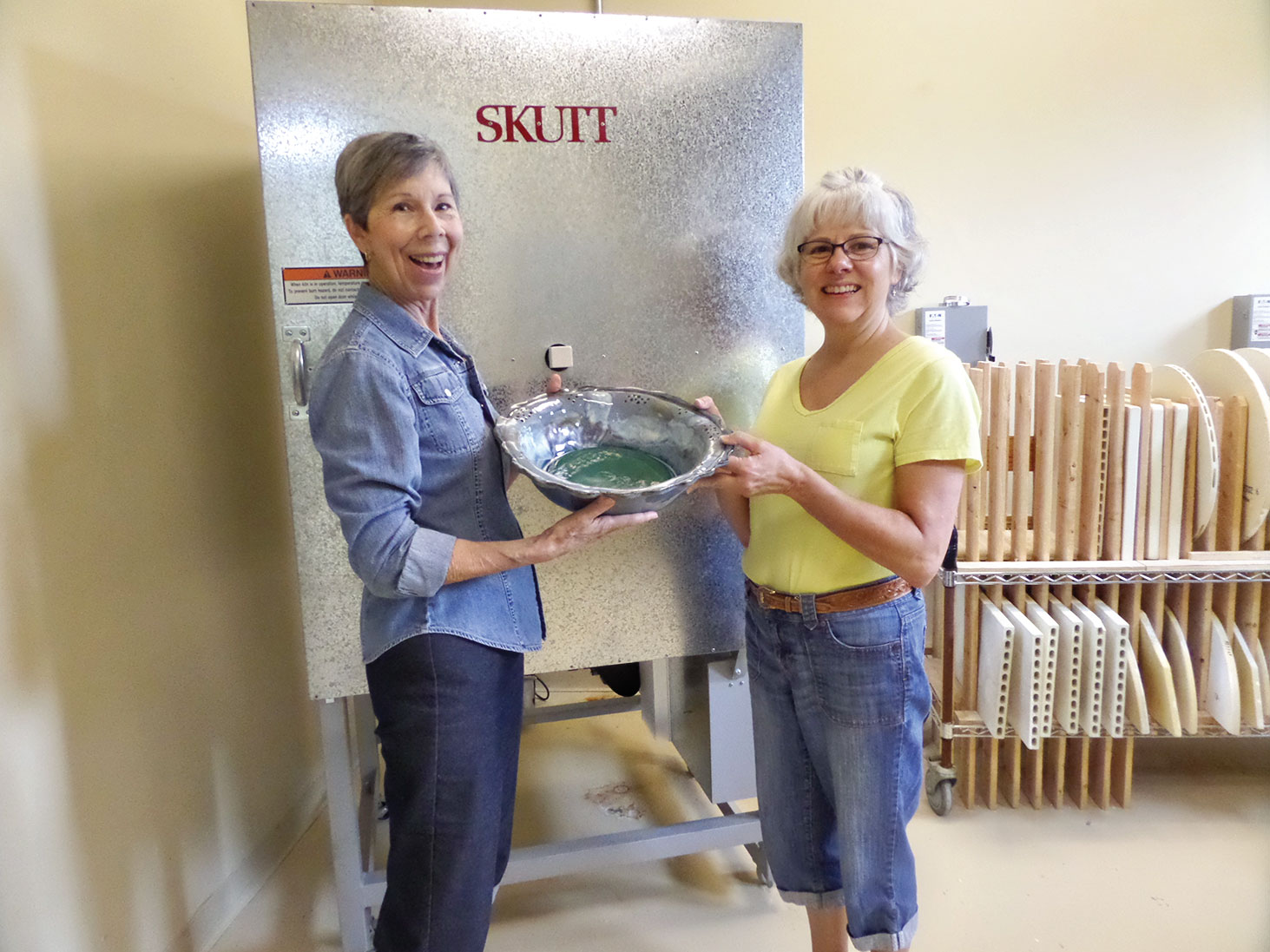 President Judie Smothers and Vice President Colleen Jordan unload a kiln.