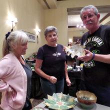 Barbara Shippy, Jackie Graham and Mike Shippy look at a bowl by Liz Katz.