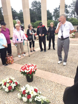 SOT President Mike Hoernemann delivers remarks to the 60 SOT travelers during the wreath laying ceremony. The roses in the foreground were later placed on individual graves by the members.