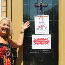 Mary Beninato displaying Victoria's welcome door