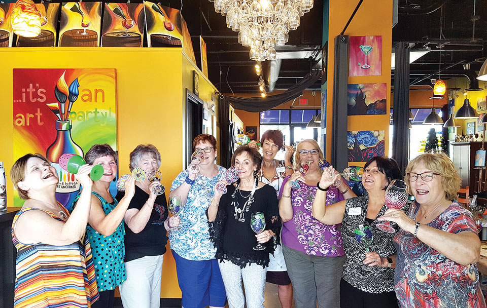 Carefully holding the freshly painted glasses, the ladies toasted their instructor. Left to right: Peggy Backes, Vicky Baker, Dorothy Hogan, Gayle Coe, Peggy Crandell, Nita Ice, Joyce Brein, Rosemary Simecek and Linda Terry
