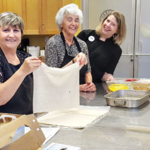 Carol Cieslik layers the phyllo for baklava while Bernadette Fidelli prepares to butter each layer while directed by a Central Market instructor.