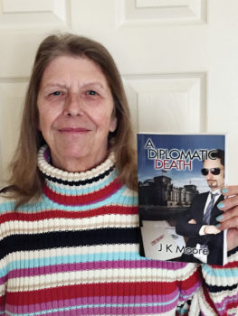J.K. Moore with her book, A Diplomatic Death