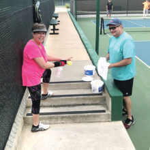 Anita Freese and Tim Trotter disinfecting a pickleball after play
