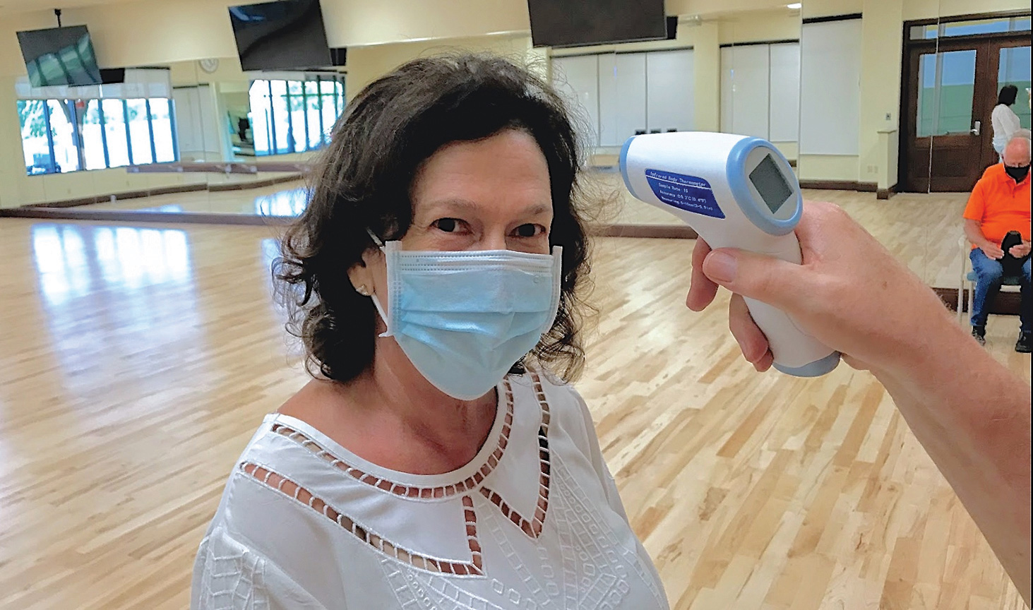 Letha Straub, a member of the social dance class, featured here passing the forehead thermometer requirement