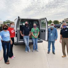 BPS Technology CEO Bravis Brown (center) and United Way of Denton County CEO Gary Henderson (right) and volunteers pose with Denton County Friends of the Family representatives, after loading their van with over 20 cases of hand sanitizer.