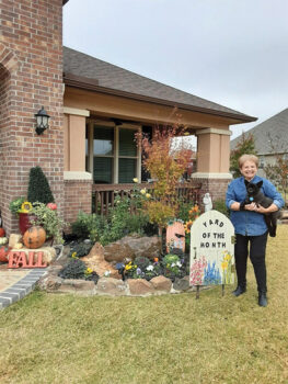 Judy Sale, holding Joy, in her November Yard of the Month.