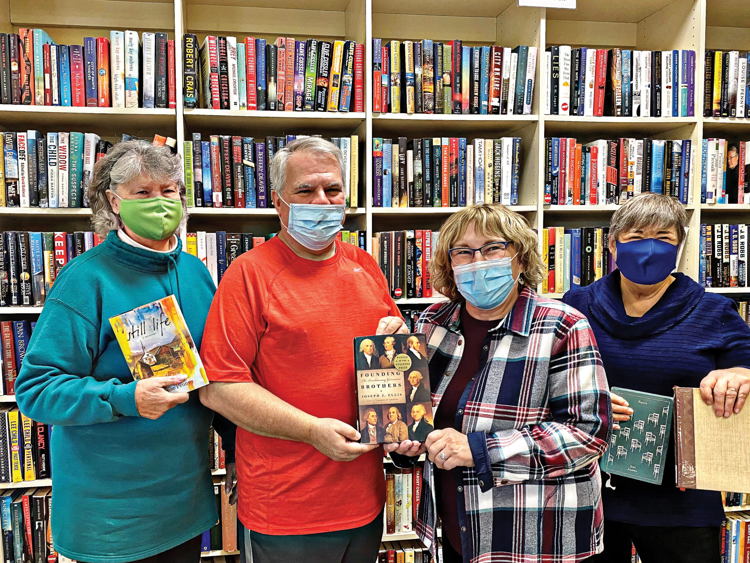 FOL donates hardcopy editions of the books scheduled for discussion in 2021. Left to right (behind the masks) are Librarian Doris Koenig, FOL Chair Alan Albarran, Library Director Linda Terry, and Librarian Diane van Naerssen.